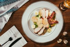 Caesar salad with chicken meat, bacon, eggs and cheese. View of ham slices with fried meat and some boiled eggs on plate over table with fork and knife on napkin stock image
