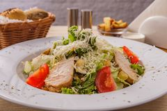 Caesar salad with chicken. Served on table stock photos