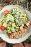 Caesar Salad con el prendedero cortado del pollo en Hay Background rústico foto de archivo