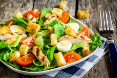 Caesar salad with croutons, quail eggs, cherry tomatoes and grilled chicken Stock Photography