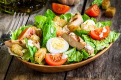 Caesar salad with croutons, quail eggs, cherry tomatoes and grilled chicken in wooden plate. On dark rustic table stock photos
