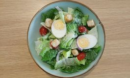 Caesar salad with eggs. Caesar salad topped with hard boiled eggs, baby tomatoes and croutons, dressed with ceasar dressing sprinkled with parmesan cheese Stock Image