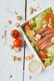 Caesar salad with fish in box on wooden surface Royalty Free Stock Photos