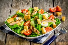 Caesar salad with grilled chicken, croutons, quail eggs and cherry tomatoes. On wooden rustic table royalty free stock photo