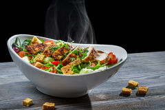 Caesar salad with hot chicken and fresh vegetables Royalty Free Stock Photos