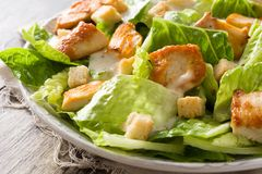 Caesar salad with lettuce,chicken and croutons on wooden table. Close up royalty free stock images