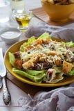 Caesar Salad mezclado en una placa amarilla Imagenes de archivo
