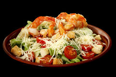 Caesar salad with prawns. On black background Stock Photo