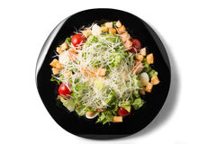 Caesar salad with prawns. Cherry tomato and cheese on black plate Royalty Free Stock Photos