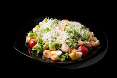 Caesar salad with prawns, cherry tomato and cheese. On black plate Royalty Free Stock Photo