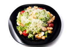 Caesar salad with prawns, cherry tomato and cheese. On black plate Stock Photography