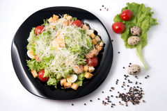 Caesar salad with prawns, cherry tomato and cheese. On black plate Royalty Free Stock Photos