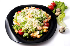 Caesar salad with prawns, cherry tomato and cheese. On black plate Stock Photos
