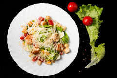 Caesar salad with prawns, cherry tomato and cheese. On white plate Stock Photo