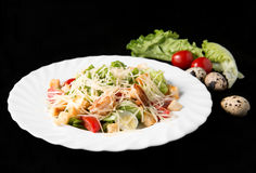 Caesar salad with prawns, cherry tomato and cheese. On white plate Stock Images