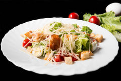 Caesar salad with prawns, cherry tomato and cheese. On white plate Royalty Free Stock Photo