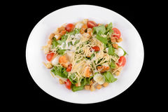 Caesar salad with prawns, cherry tomato and cheese. On white plate on black background Stock Photography