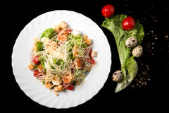 Caesar salad with prawns, cherry tomato and cheese. On white plate, isolated Royalty Free Stock Photography