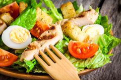 Caesar salad with quail eggs, cherry tomatoes and grilled chicken close up Stock Photography