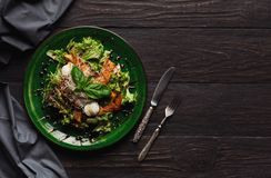 Caesar salad with quail eggs and chicken meat. Fresh side dish with vegetables on black table with cutlery, restaurant serving, top view, copy space Royalty Free Stock Image