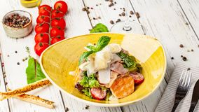 Caesar salad with salmon. mix of salads, cherry tomatoes, parmesan cheese, basil. A dish in a ceramic plate is on a wooden table. In a restaurant. A glass of royalty free stock photography