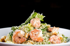 Caesar salad with shrimp. A white dish with Caesar salad and shrimp on dark background Stock Photo