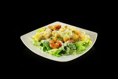 Caesar salad with shrimps. Caesar salad with prawns on a black background Royalty Free Stock Photos
