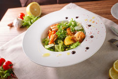 Caesar salad with shrimps and iceberg leaves. Caesar salad with shrimp on a white plate Royalty Free Stock Images