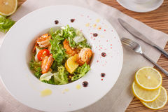 Caesar salad with shrimps and iceberg leaves. Caesar salad with shrimp on a white plate Royalty Free Stock Photo