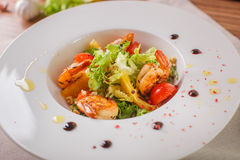 Caesar salad with shrimps and iceberg leaves. Caesar salad with shrimp on a white plate Stock Photos