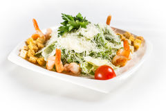 Caesar salad with shrimps. On white plate Stock Photography