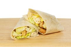 Caesar salad wraps. Chicken Caesar salad bread wraps on a wooden board against a white background royalty free stock images