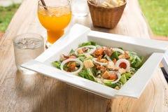 Caesar-Salat in der weißen Platte, Orangensaft, Glas Wasser auf woode Stockfotografie