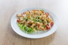Caesar-Salat mit Huhn auf Holztisch Stockbild