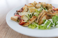 Caesar-Salat mit Huhn auf Holztisch stockfotos