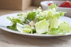 Caesar-Salat mit Tomaten im Hintergrund Stockbilder