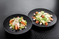 Caesar sallad med räkor och sallad med laxen, gräddost och gurkan på svarta plattor på en mörk bakgrund arkivbilder