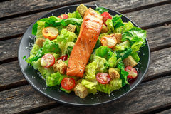 Caesar Salmon Salad with croutons, parmesan cheese, tomatoes, dressing and pepper in a black plate on wooden table. Stock Image