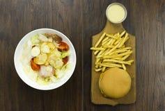 Caesar sauce salad cheeseburger fries delicious healthy food tomatoes croutons Parmesan cheese Royalty Free Stock Photography