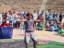 A participant of the Purim festival juggles with hoops for visitors in Caesarea, Israel. Caesarea, Israel, March 03, 2018 : A participant of the Purim festival Royalty Free Stock Image