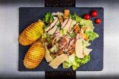 Caesars salad on black background. Caesars salad on black and silver background Stock Image
