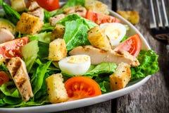Caesarsalade met dicht omhoog croutons, kwartelseieren, kersentomaten en geroosterde kip Stock Foto