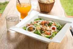 Caesarsalade in Witte plaat, Jus d'orange, Glas water op woode Stock Fotografie