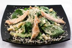 Caeser salad. On black plate Stock Photography