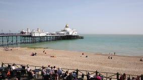 Café ocupado de Eastbourne Sussex Inglaterra, com povos, praia e cais no tempo bonito da mola vídeos de arquivo