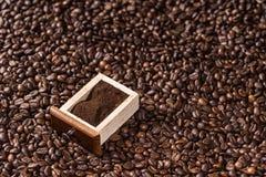 Cafè moulu dans la boîte sur le fond de grains de café Image libre de droits