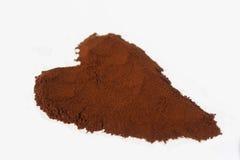 Cafè moulu dans la forme du coeur d'isolement sur le blanc Photo stock