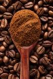 Cafè moulu dans une cuillère de vintage sur des grains de café Photos stock