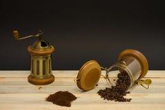 Cafè moulu dispersé de grains de café et broyeur de café manuelle sur les conseils en bois et sur le fond noir photographie stock