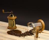 Cafè moulu dispersé de grains de café et broyeur de café manuelle sur les conseils en bois et sur le fond noir photos stock